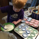Scooping the cake batter into the cupcake liners.