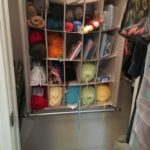 The shoe organizer, with yarn and other stuff, hanging on the back wall of the closet.